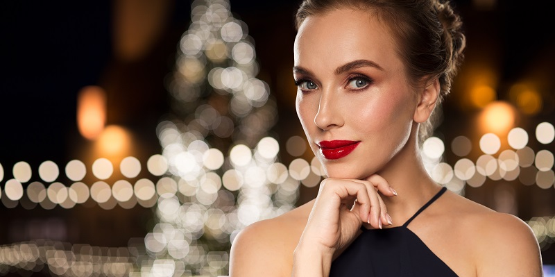 Woman posing in front of a Christmas tree looking glamorous after facial rejuvenation