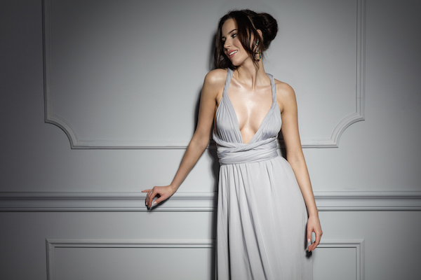Image of a woman in a low-cut dress leaning against a dimly-lit wall.