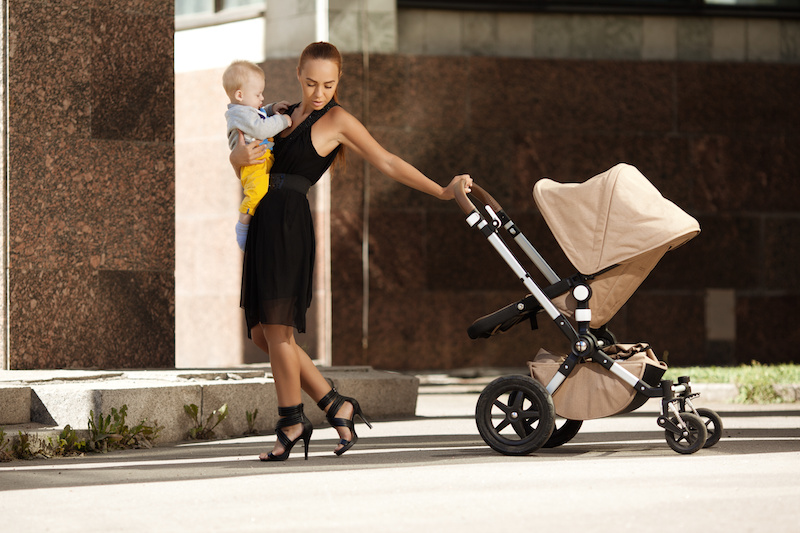Stylish, fit mom in black dress and heels carrying baby and holding a stroller