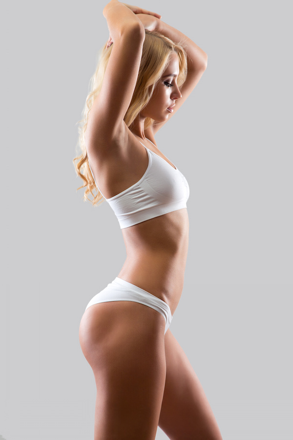 Slim blonde woman viewed from side, in white bra and underwear set after breast augmentation